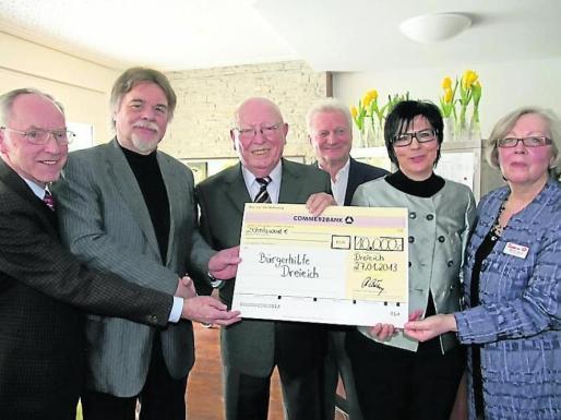 Klaus Hellweg (2.v.l.), Vorsitzender der Bürgerhilfe nahm von Robert Lösch (3.v.l.) den Scheck über 10 000 Euro entgegen. Foto: Jost